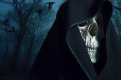 Skeleton in a black hood. Stock Images