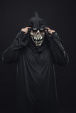 Skeleton in a black robe corrects glasses Stock Images
