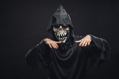 Skeleton in a black robe with glasses dancing. Jolly skeleton  in a black robe with glasses dancing in the dark under the rays of the moon Royalty Free Stock Image