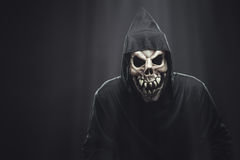 Skeleton in a black robe standing under rays Stock Photography