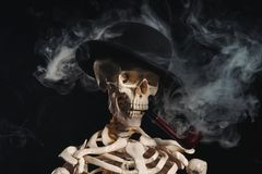 Skeleton in bowler hat smoking pipe Royalty Free Stock Photography