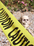 Skeleton and Caution Tape. Skeleton on the ground surrounded by caution tape royalty free stock images