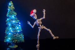 Christmas Spirit. A skeleton dancing around a Christmas Tree with lights stock images
