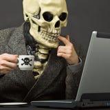 Skeleton drinks poisonous coffee with laptop Stock Photo