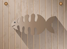 Skeleton fish with shadow on brown wooden texture background Royalty Free Stock Images