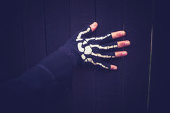 Skeleton glove wearing hand touching a fence Royalty Free Stock Photo