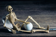 Skeleton with golf. Skeleton sitting with golf equipment on old wood royalty free stock image