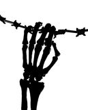 Skeleton hand and barbed wire. Silhouette of a skeleton hand holding barbed wire stock photo