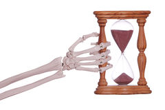 Skeleton hand holding sand timer Stock Image