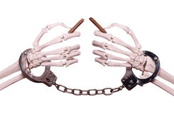 Skeleton hands with handcuff holding broken cigar royalty free stock photography