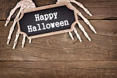 Skeleton hands holding a Happy Halloween tag. Over an old rustic wood background Royalty Free Stock Photo