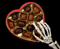 Skeleton hands selects a chocolate. From a heart shaped candy box, isolated on black stock images