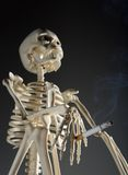 Skeleton holding cigarette  Stock Photography