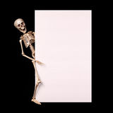 Skeleton holding empty blank over black. Halloween Royalty Free Stock Photo
