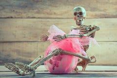 Skeleton hug gift on wood background. Stock Image