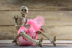 Skeleton hug gift on wood background. Royalty Free Stock Photography