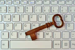 Skeleton key and keyboard. An old skeleton key rests on top of a modern keyboard stock photos