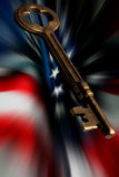 Skeleton Key and US flag. An old brass key and motion blurred US flag Royalty Free Stock Photo
