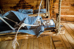 Skeleton lying in bed. Skeleton is lying in hanging wooden bed Royalty Free Stock Image