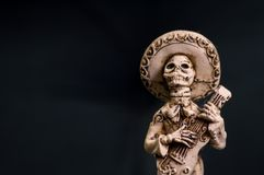 Skeleton Mexican mariachi groom wedding cake topper hand carved from bone. Male holding guitar figurine. Space for text royalty free stock image