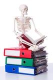Skeleton with pile of files. On white Stock Photo