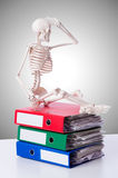 Skeleton with pile of files against gradient Stock Photos