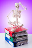 Skeleton with pile of files against gradient Stock Photo