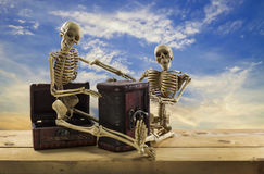 Skeleton pirate sitting on a treasure chest and old wood floor,b Royalty Free Stock Photo