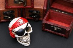 Skeleton pirate with treasure chest. On dark background stock photography