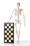 The skeleton playing chess game on white Royalty Free Stock Images