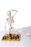 The skeleton playing chess game on white Royalty Free Stock Image