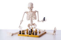 The skeleton playing chess game on white Royalty Free Stock Photography
