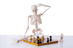 The skeleton playing chess game on white Stock Photography