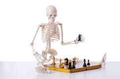 Skeleton playing chess game on white Royalty Free Stock Photos