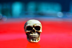 Skeleton on a red sports muscle car. Hood Royalty Free Stock Images