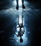 Skeleton reflection in puddle royalty free stock photos