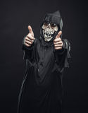 Skeleton in a robe showing thumbs up Stock Photos