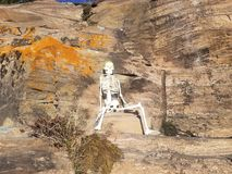 Skeleton on a rock wall royalty free stock photos