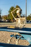 Skeleton scratches head. Trying to figure out next chess move royalty free stock image
