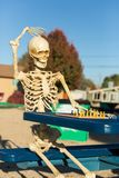 Skeleton scratches head. Trying to figure out next chess move stock images