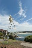 Skeleton Sculpture by the Sea Bondi Beach. Skeleton up a ladder Sculpture at Sculptures by the Sea Bondi Beach with One of the Scultures featured in the Stock Photos