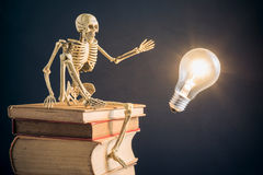 Skeleton sitting on old book. Still life photography : intellect concept with skeleton sitting on stack of old book, he have the great idea stock photos