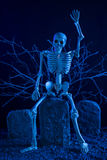 Skeleton sitting on a tombstone Royalty Free Stock Images