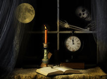 Skeleton Tapping on Window Pane. Reading glasses on open book, candle flame and full moon casting yellow glow over book and table while skeleton is outside stock image