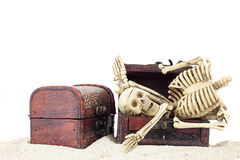 Skeleton in a treasure chest on pile sand isolated on white back royalty free stock photography