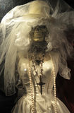 Skeleton in wedding dress. Half body portrait of skeleton in retro style wedding dress with crucifix around neck royalty free stock images
