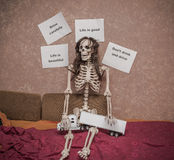Skeleton in a wig sitting on the bed with truck and trailer model on his legs, leaning against the wall with various messages Royalty Free Stock Image
