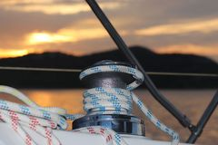 Skeleton winch on board a sailing cruise yacht. The view from the cockpit on the sunset background. Quiet and calm morning. Yachting holiday. Boat charter in royalty free stock photography