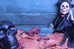 Skeleton witch and black skull over autumn leaves on wooden background, toned in blue. Halloween concept.  stock image