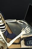 Skeleton at Work 2. A skeleton works on a laptop computer Stock Images